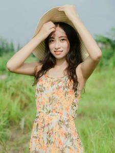 草地上的长裙草帽美女明媚笑容