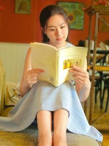 咖啡馆内的丸子头娇美姑娘沉浸书本