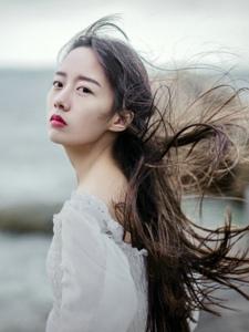 海岸边的白裙长发红唇美女秀发飘逸