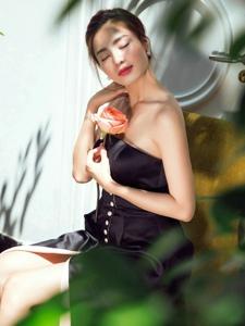 沙发上的抹胸时尚百褶裙美模拿着花享受阳光照射