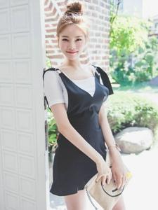 站在大门口的可爱搞怪丸子头嫩模黑色连衣裙
