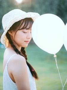 阳光下的草地有着明媚气球少女