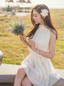 晴天花园内的捧花美模洁白纱裙柔美动人