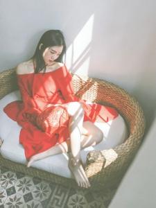 鲜花美女裸肩红裙赤脚坐在地上神情忧郁