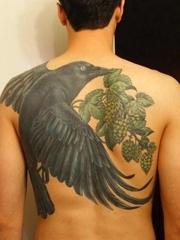 男性后背大面积黑色乌鸦和啤酒花纹身图案