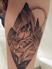 手小臂膀上的菱形形状的睡觉的岩石巨人纹身图片