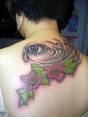 女性后背逼真的彩绘眼睛和花纹身