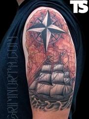大臂上一款精细的帆船指南针纹身图案