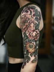 女性左手大臂膀漂亮的花朵纹身图案