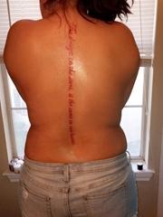 女子背部脊椎骨上一行红色的英文字纹身图片
