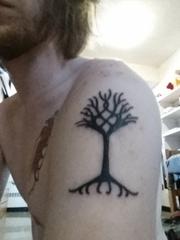男性左手臂上黑色的小树图腾纹身图片