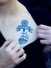 女生胸前的蓝色帆船字母图章纹身