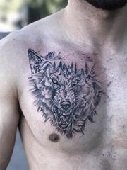 男性胸部上黑灰色山峰和狼头纹身图片