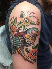 男性右手臂上彩色的鸟纹身小花朵纹身图片