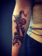 手臂毒蛇缠绕匕首个性纹身图片