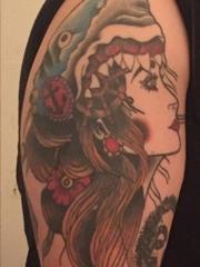 右手大臂膀上的漂亮鲨鱼头饰女子纹身