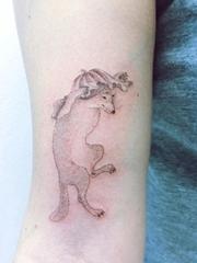 手臂上的一只用莲叶盖头上的狐狸图片纹身