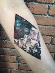 手前臂上的菱形里的彩色星空山峰和树木纹身