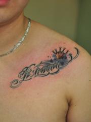 男人肩部处精美时尚的字母与皇冠纹身图案