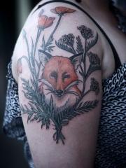 女性手臂上花丛中的狐狸纹身图案