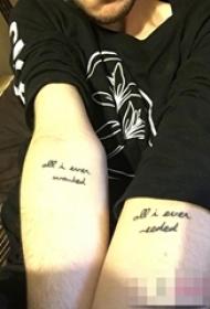 男生手臂上黑色抽象线条英文短句纹身图片