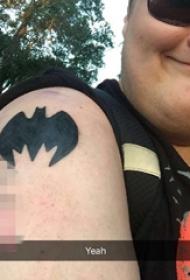 女生手臂上黑色轮廓蝙蝠侠图标纹身图片