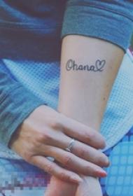 女生手臂上黑色几何线条英文单词和心形纹身图片