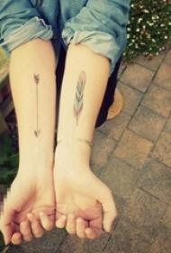 女生手臂上彩绘渐变简单线条羽毛和箭头纹身图片