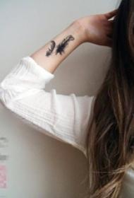 女生手腕上黑色点刺轻盈羽毛纹身图片