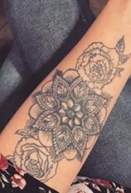女生手臂上黑色点刺抽象线条植物花朵纹身图片