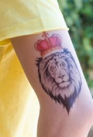 男生手臂上彩绘皇冠和黑灰点刺狮子纹身图片