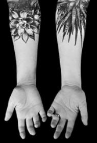 女生手臂上黑色点刺简单线条植物叶子和花朵纹身图片