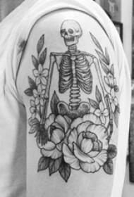 男生大臂上黑灰点刺简单线条花朵和骷髅骨架纹身图片