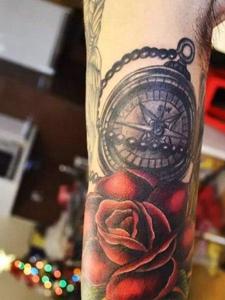 指南针和玫瑰花一起的手臂纹身