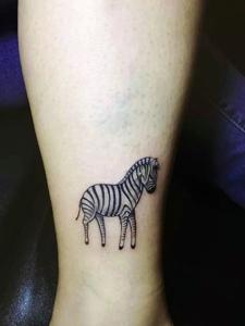 裸脚下的一匹可爱小斑马纹身图片