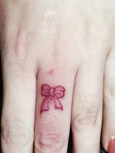 小小的蝴蝶结纹身落在小手上特别好看
