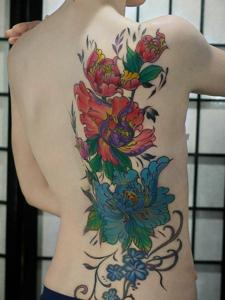 遮盖女生半边背部的彩色牡丹花纹身刺青