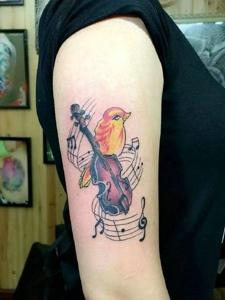 一只爱音乐的小鸟手臂纹身刺青