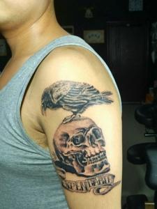 站在骷髅头上的小鸟手臂纹身图案