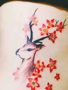 遮盖后背的五角星花朵与小鹿纹身图案