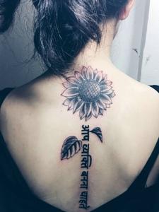 向日葵与梵文结合的脊椎部纹身图案
