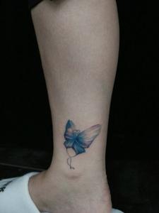 裸脚侧边上的彩色蝴蝶纹身图案