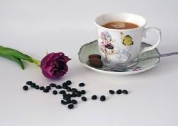 咖啡豆散落在装有咖啡的杯子旁图片_10张