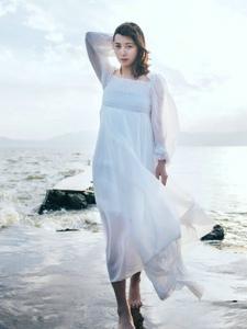 海边一字肩白裙美女自由随风飘动