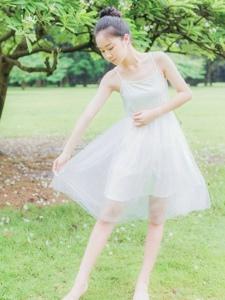 草地上的丸子头白纱吊带舞裙轻盈吸睛