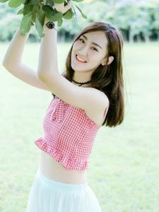 草地上的吊带露脐装美女笑容阳光灿烂