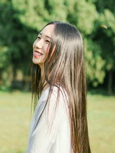 草地上的长发女神散发淳朴笑容