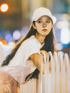 夜晚街头上的棒球帽阔腿裤美女独自一人