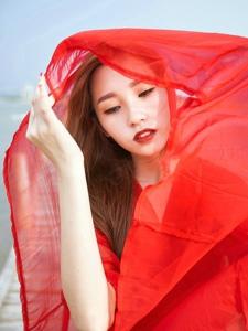 鲜艳红裙美模海边被风吹长发飘逸手捧花令人怜爱