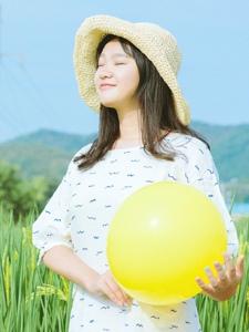 清新田野中的圆脸少女笑容阳光灿烂